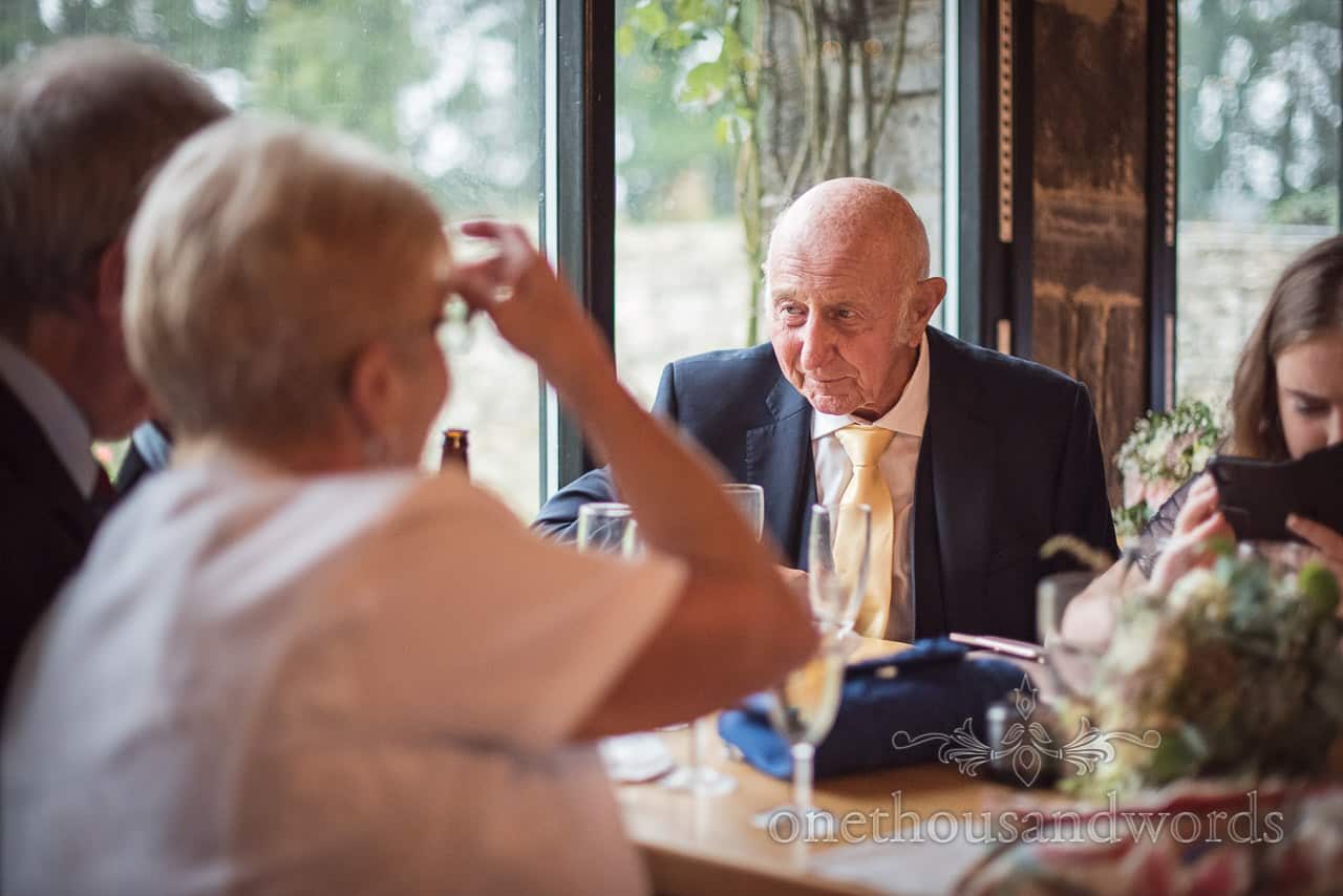 Elderly wedding guest enjoy bar drinks at reception at Kingston barn wedding photograph by one thousand words photography