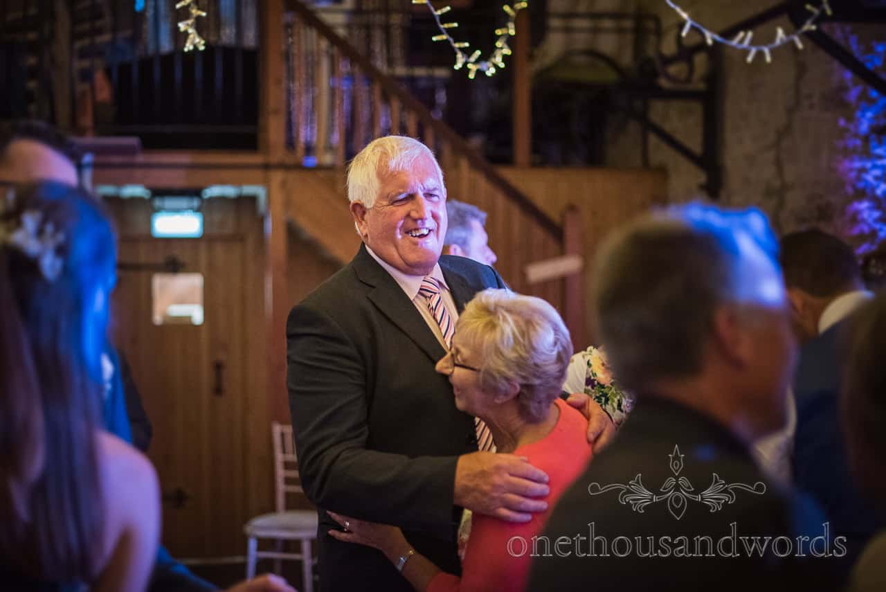 Wedding guests dance under disco lights during evening reception at barn wedding in Dorset by one thousand words photography