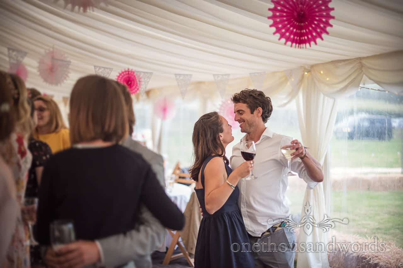 Documentary wedding photograph of smiling wedding guests intimate dance with drinks in hand in wedding marquee