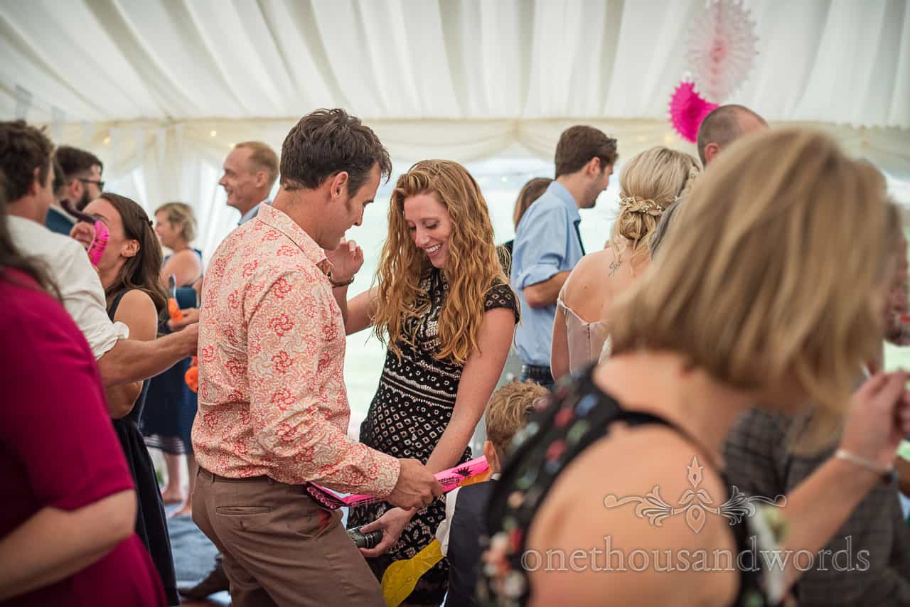 Documentary wedding photograph of wedding guests playing with inflatable instruments on marquee dance floor