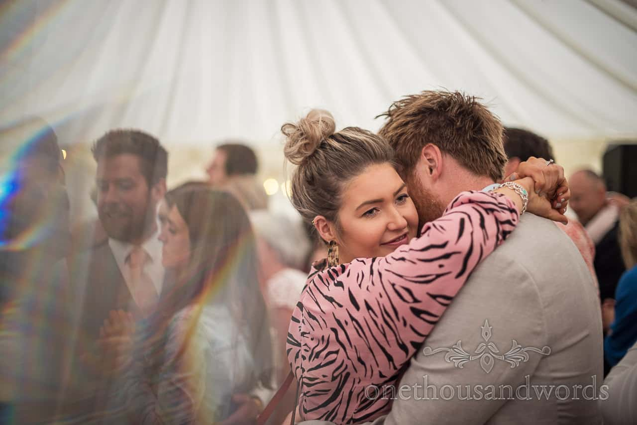 Happy wedding guests embrace whilst dancing at a Purbeck farm marquee wedding photographs by one thousand words photography
