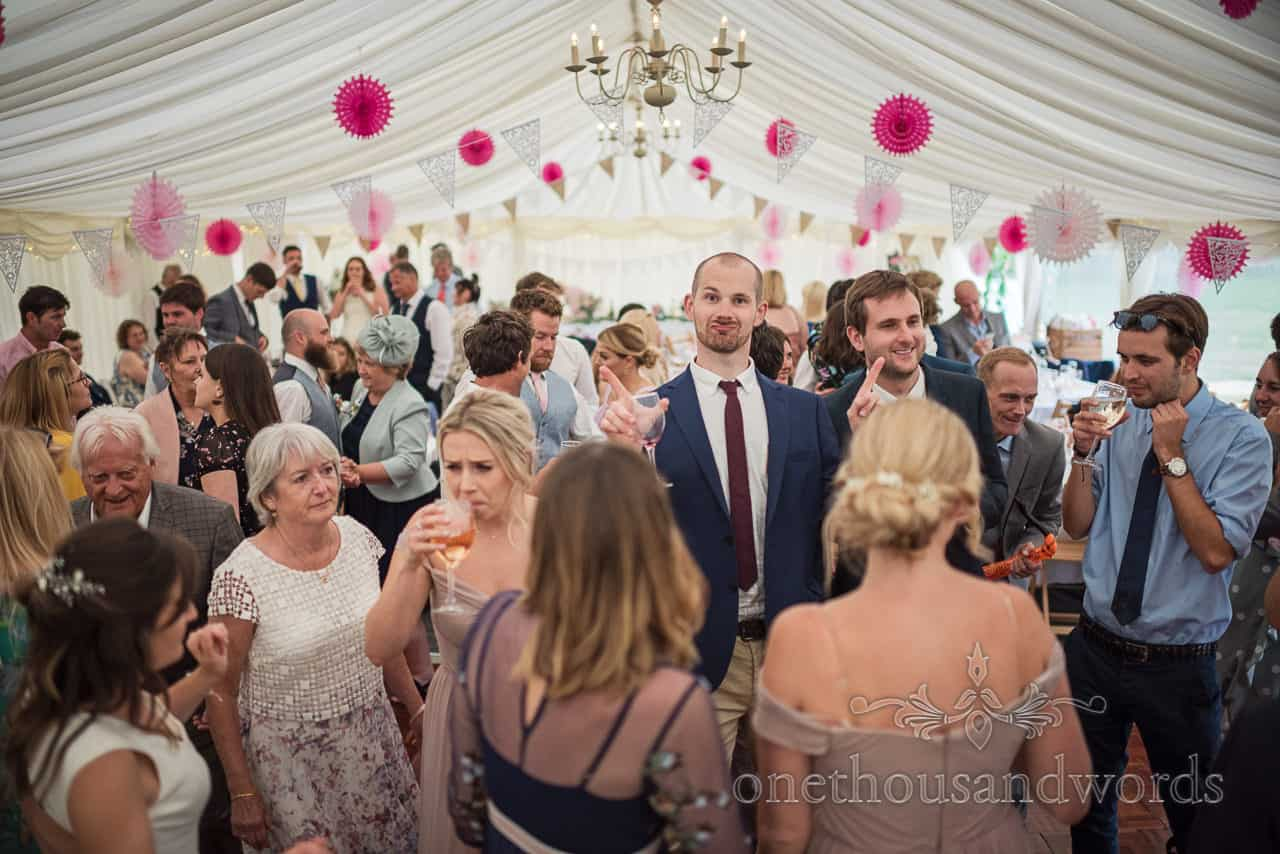 Wedding guests gathered on the dance floor at Purbeck farm marquee wedding photographs by one thousand words photography