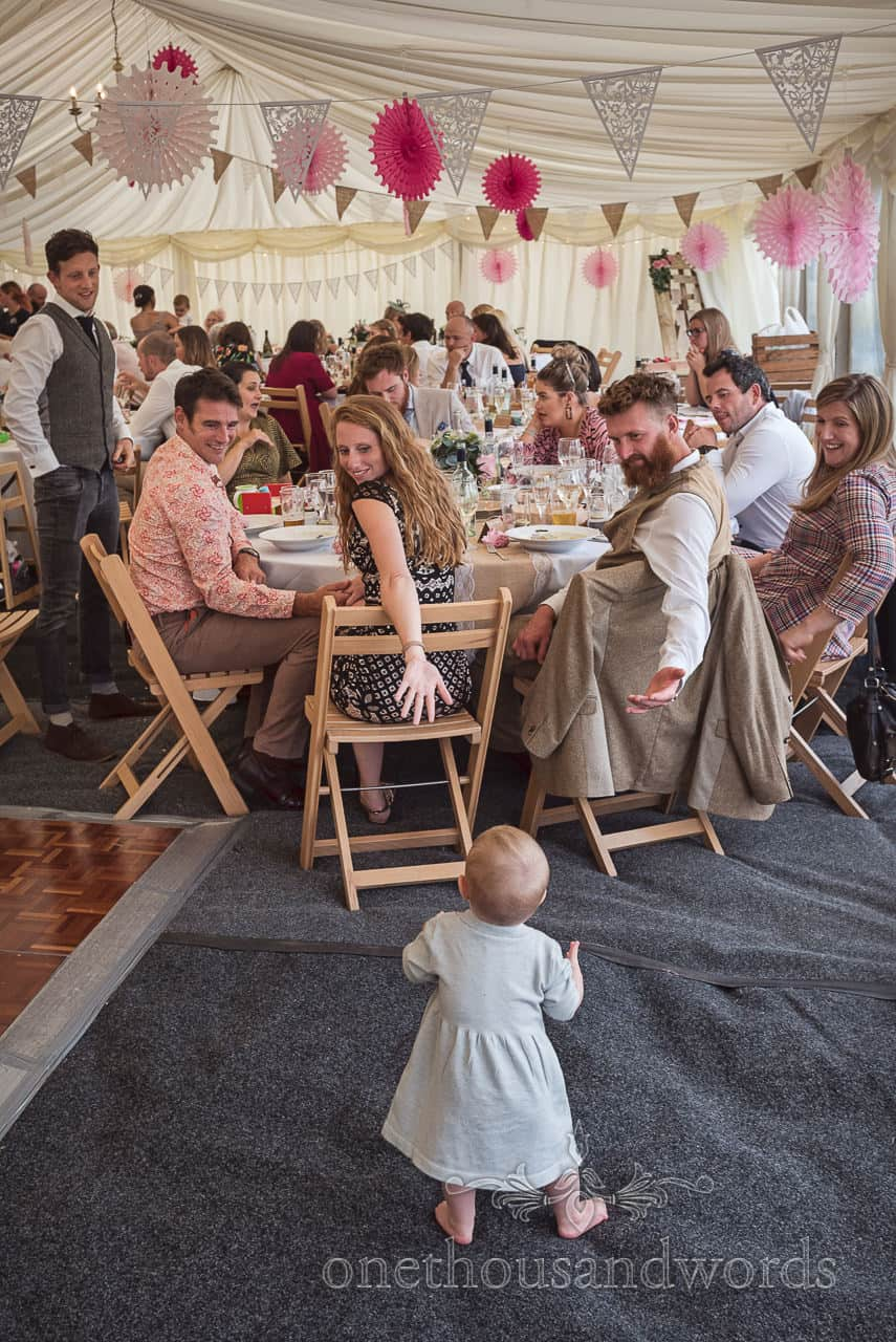 Table of wedding guests interacting with a baby during marquee wedding breakfast