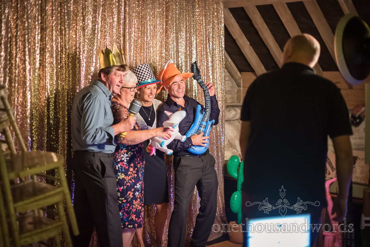 Wedding guests pose in fancy dress with props in photo booth at barn wedding in Dorset by one thousand words wedding photography