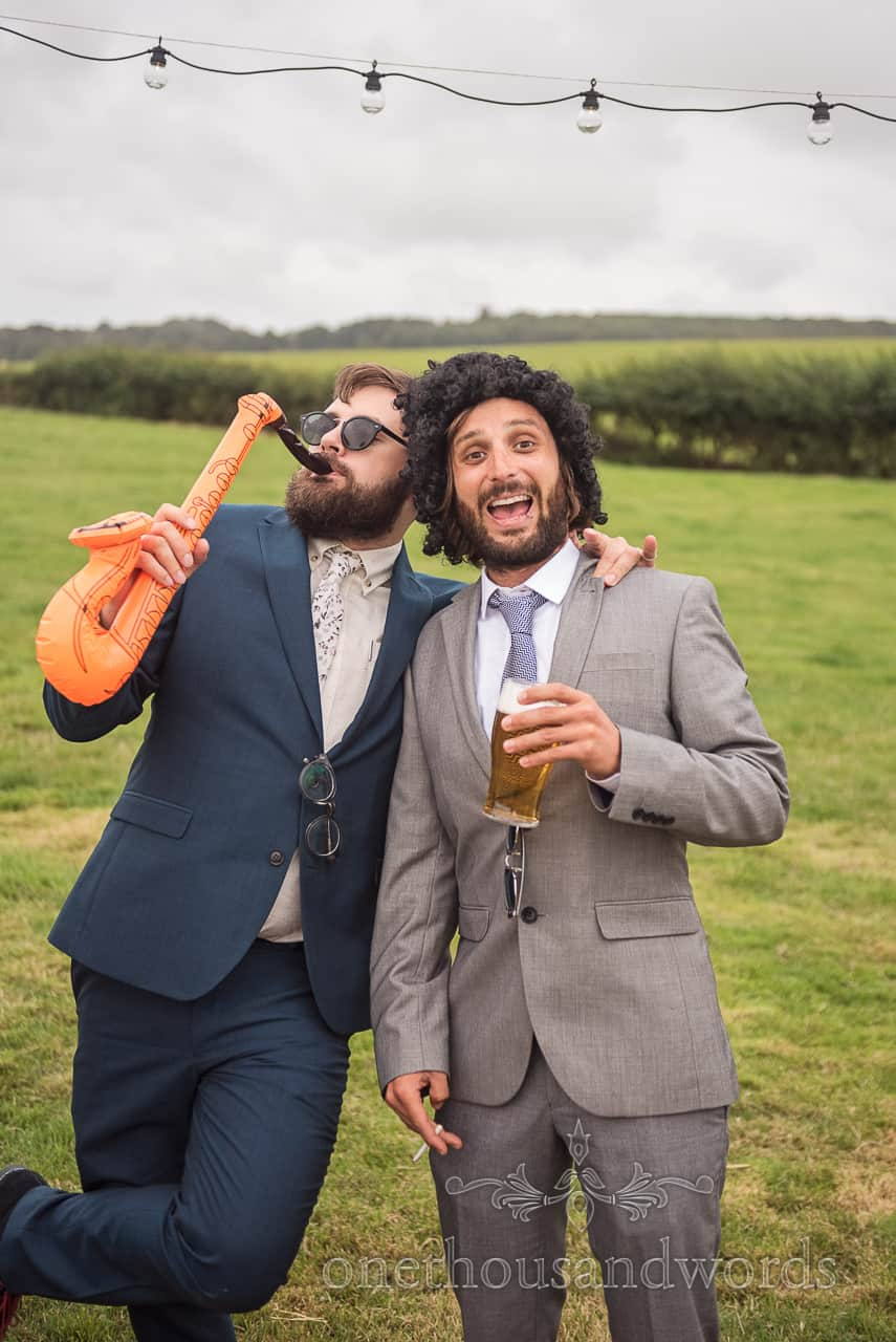 Wedding guests pose in Dorset countryside field with fancy dress and photo booth props