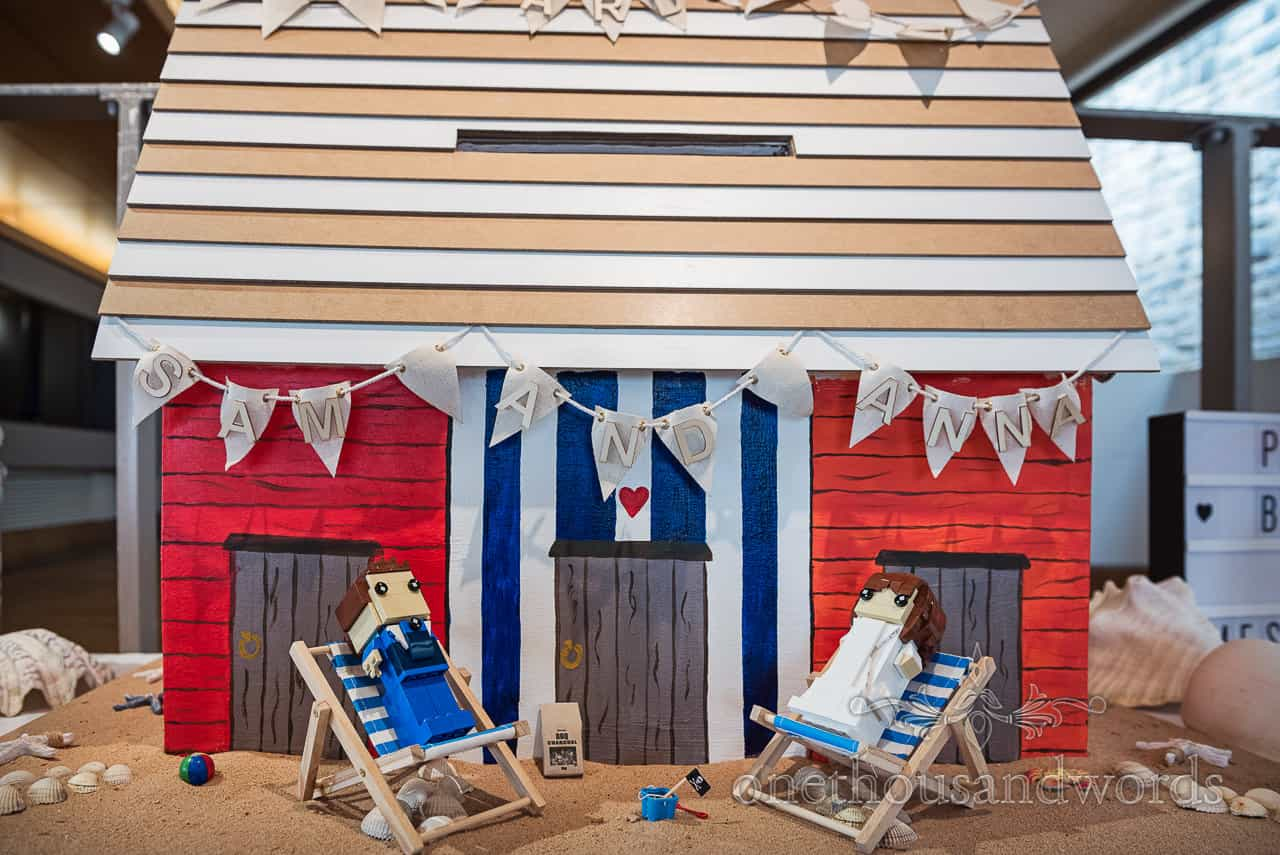 Handmade beach hut wedding card box with Lego bride and groom on deckchairs and bunting with names