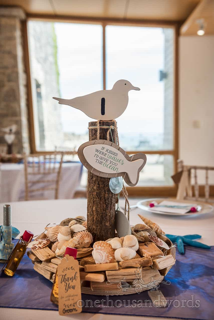 Handmade sea side themed wedding table number centrepiece with seagull, fish shaped sign, wooden log and sea shells