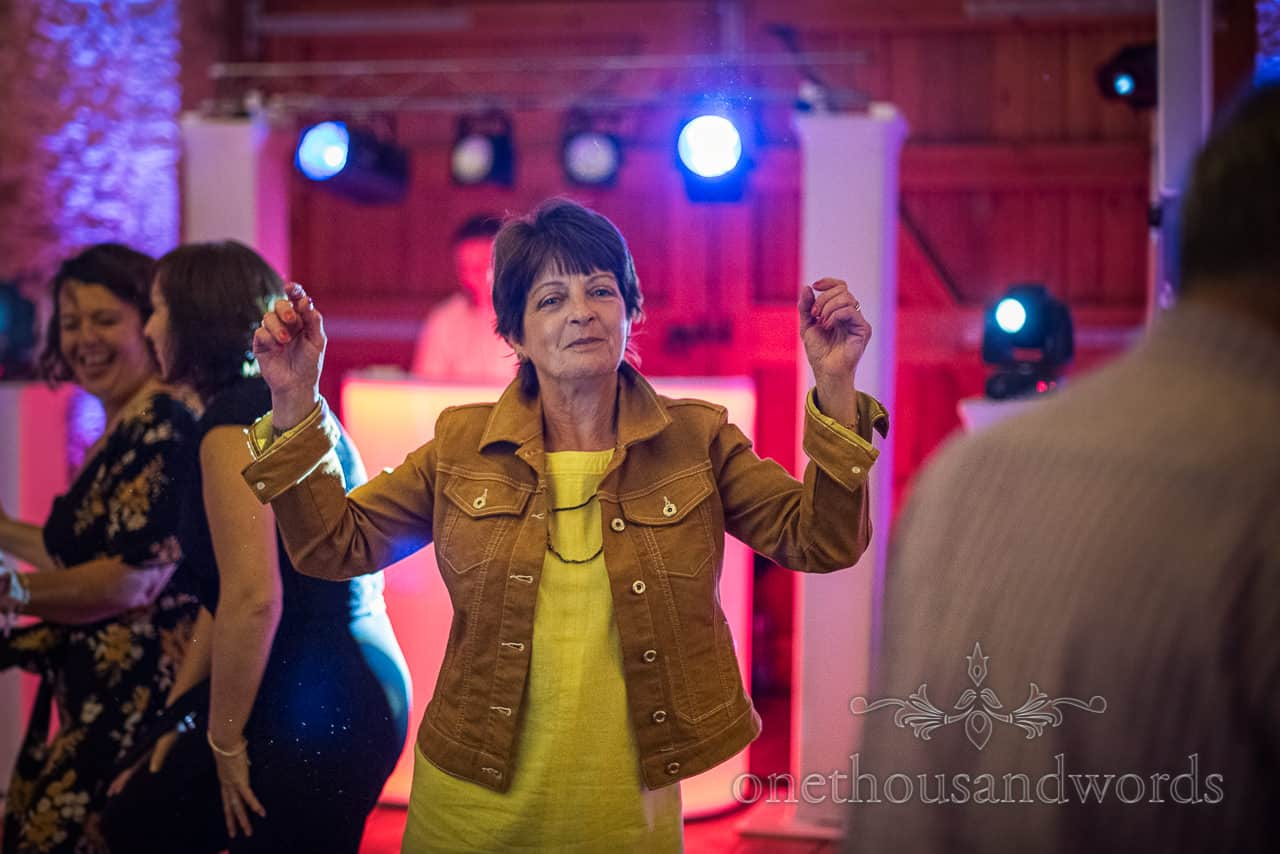 Wedding evening guest with hands in air dancing to DJ with disco lights at Kingston barn wedding venue in Dorset