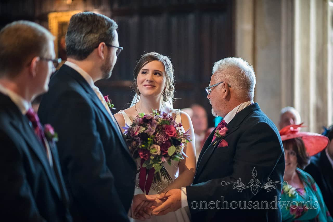 Happy bride smiles at groom as he takes her hand in marriage at Athelhampton House wedding ceremony photograph