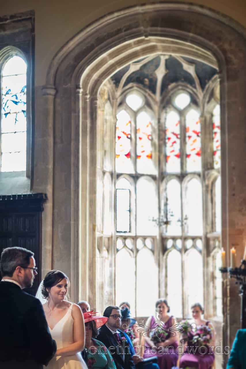 Happy bride photographed during wedding ceremony with oriel window at Athelhampton House wedding venue by one thousand words