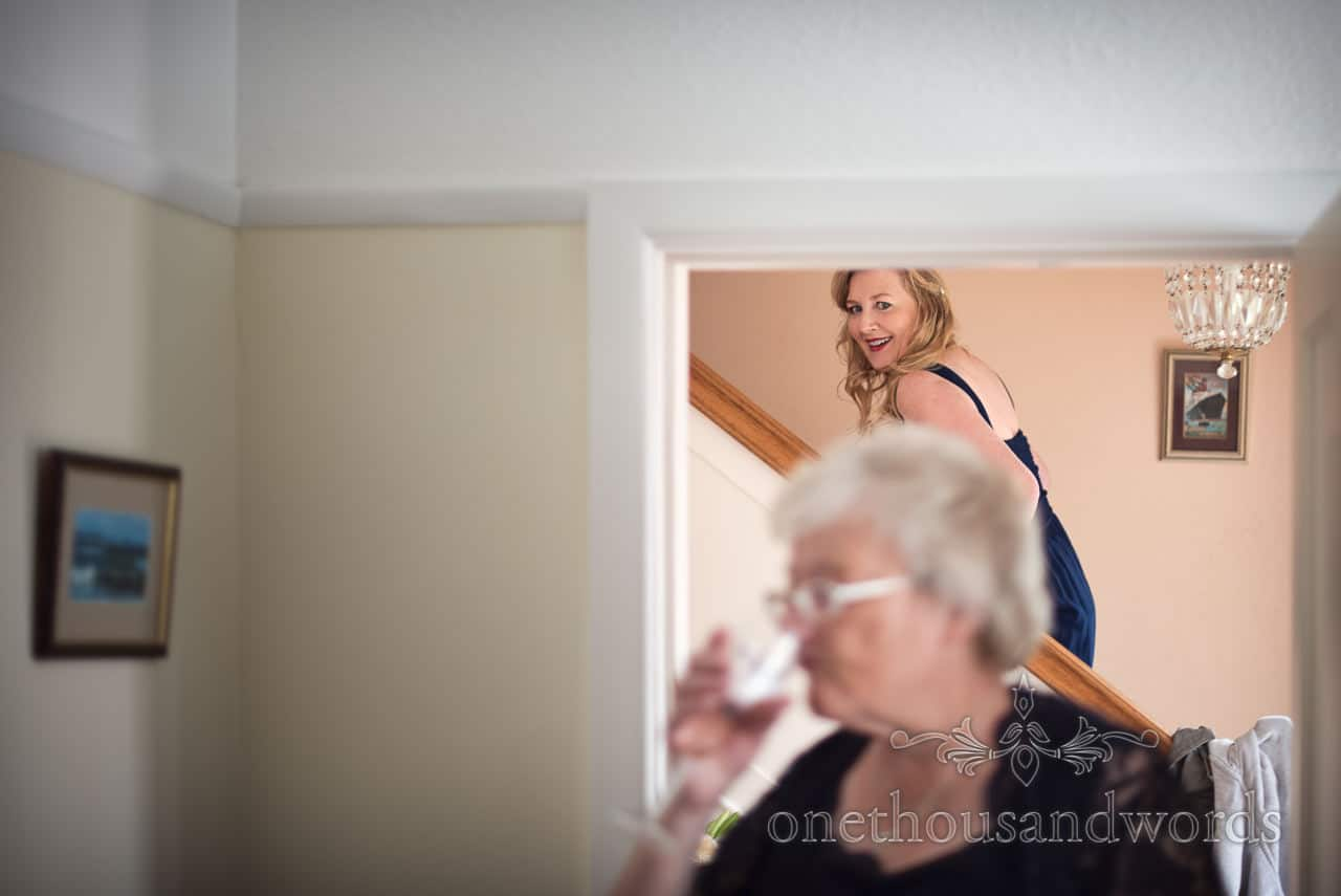 Documentary wedding photograph of happy bridesmaid walking up Staircase whilst mother of bride drinks champagne