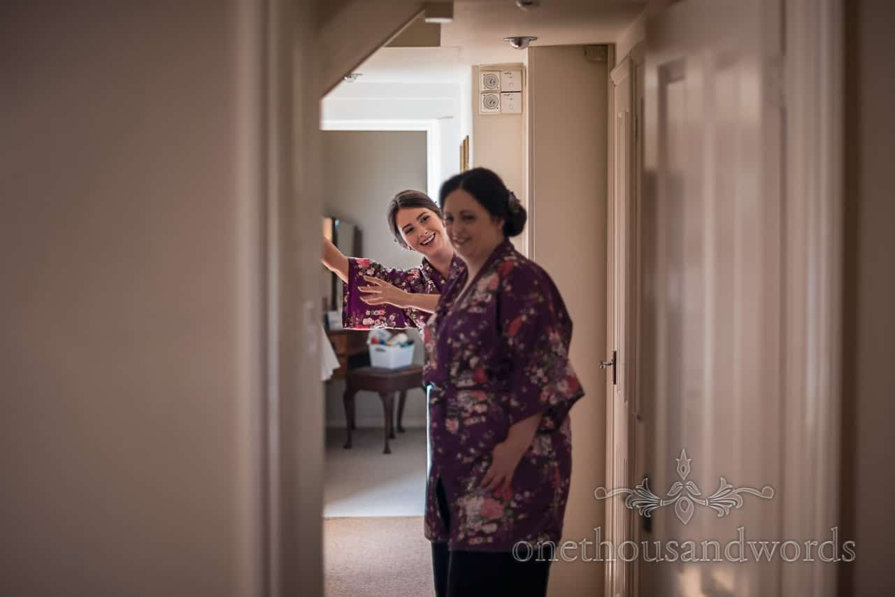 Happy bridesmaids wearing purple floral dressing gowns laughing during Athelhampton House wedding morning preparations