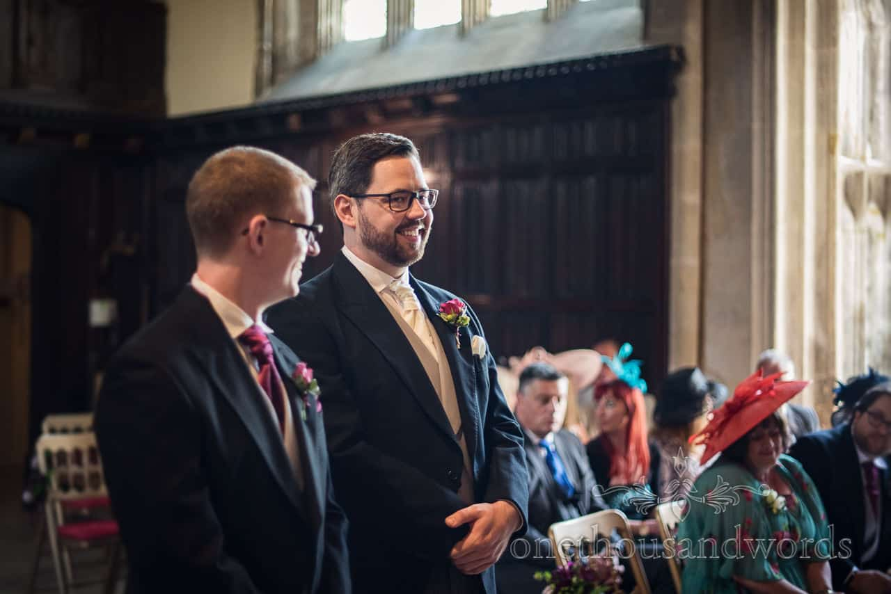 Happy groom waiting with best man for bride to arrive at Athelhampton House wedding ceremony photograph by one thousand words