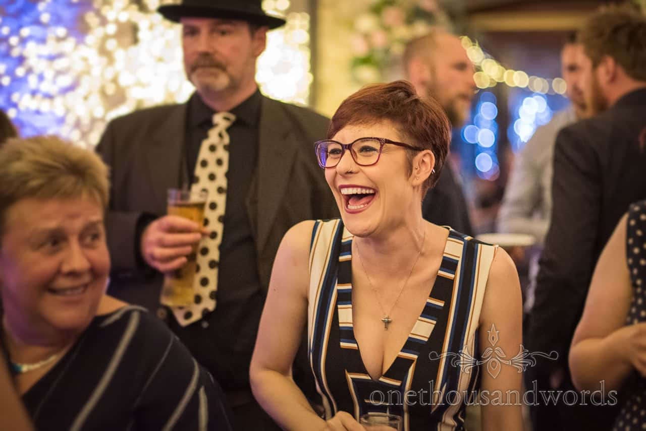 Wedding guest laughing at evening reception in fairy lit barn wedding venue in Dorset by one thousand words wedding photographers