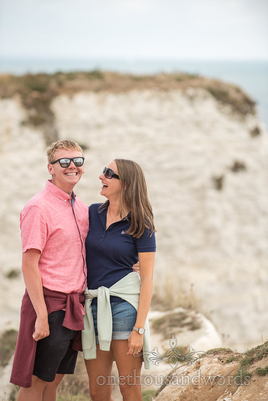 Old Harry Rocks engagement photograph of couple laughing by white cliffs and sea views by one thousand words photography in Dorset