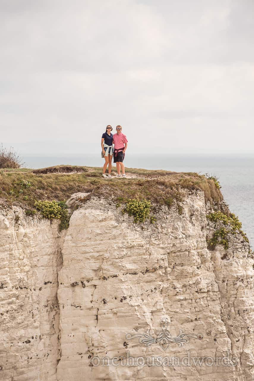 Old Harry Rocks engagement photographs of couple on chalk cliff top by one thousand words documentary wedding photography