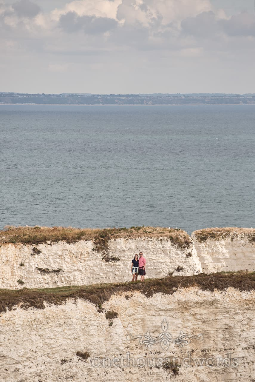 Old Harry Rocks engagement photograph of happy couple in distance on Dorset white cliffs by one thousand words photographers