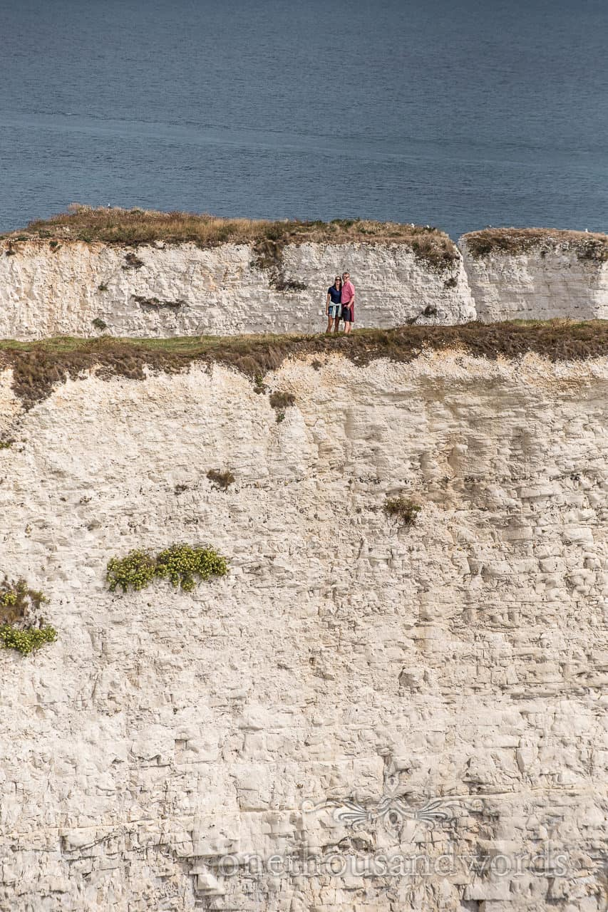 Old Harry Rocks engagement photographs of engaged couple taken from a distance by one thousand words wedding photography