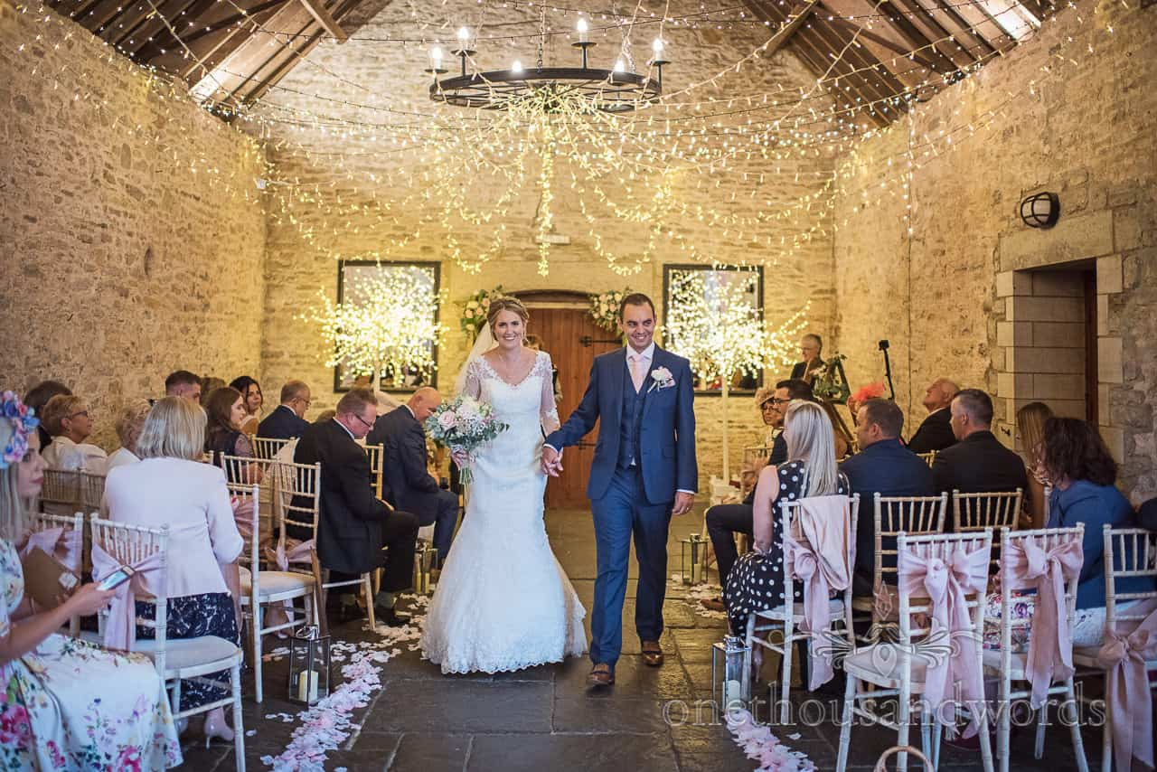 Bride and groom walk down the aisle at Kingston Country Courtyard wedding photographs by one thousand words photogrpahy in Dorset