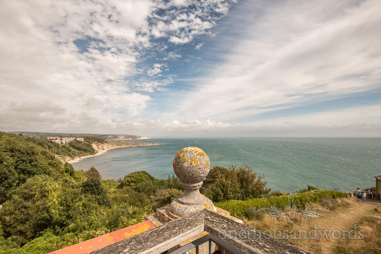 Stunning Jurassic coastal view from Durlston Castle wedding venue in Dorset with summer blue sky and clouds by one thousand words