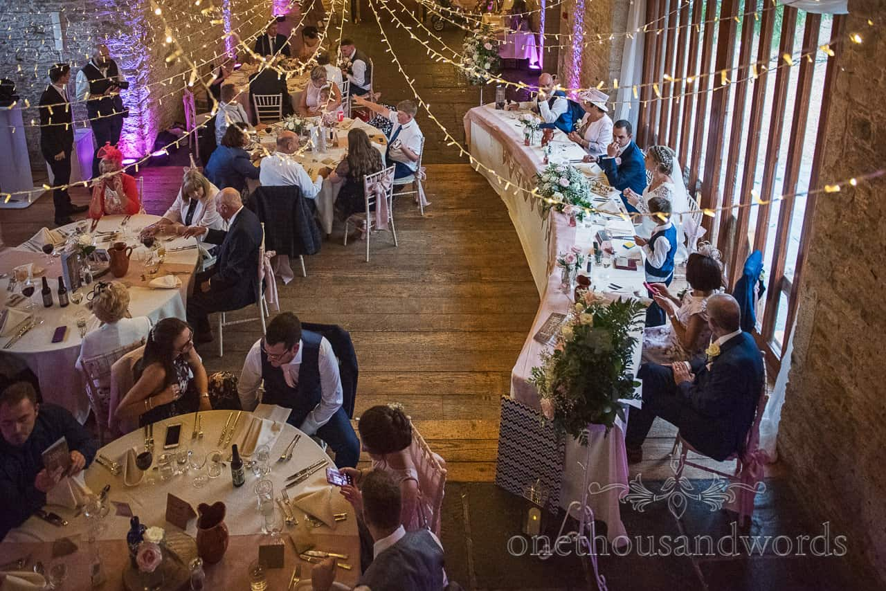 Kingston Country Courtyard wedding venue in Dorset wedding breakfast under fairy lights photograph by one thousand words