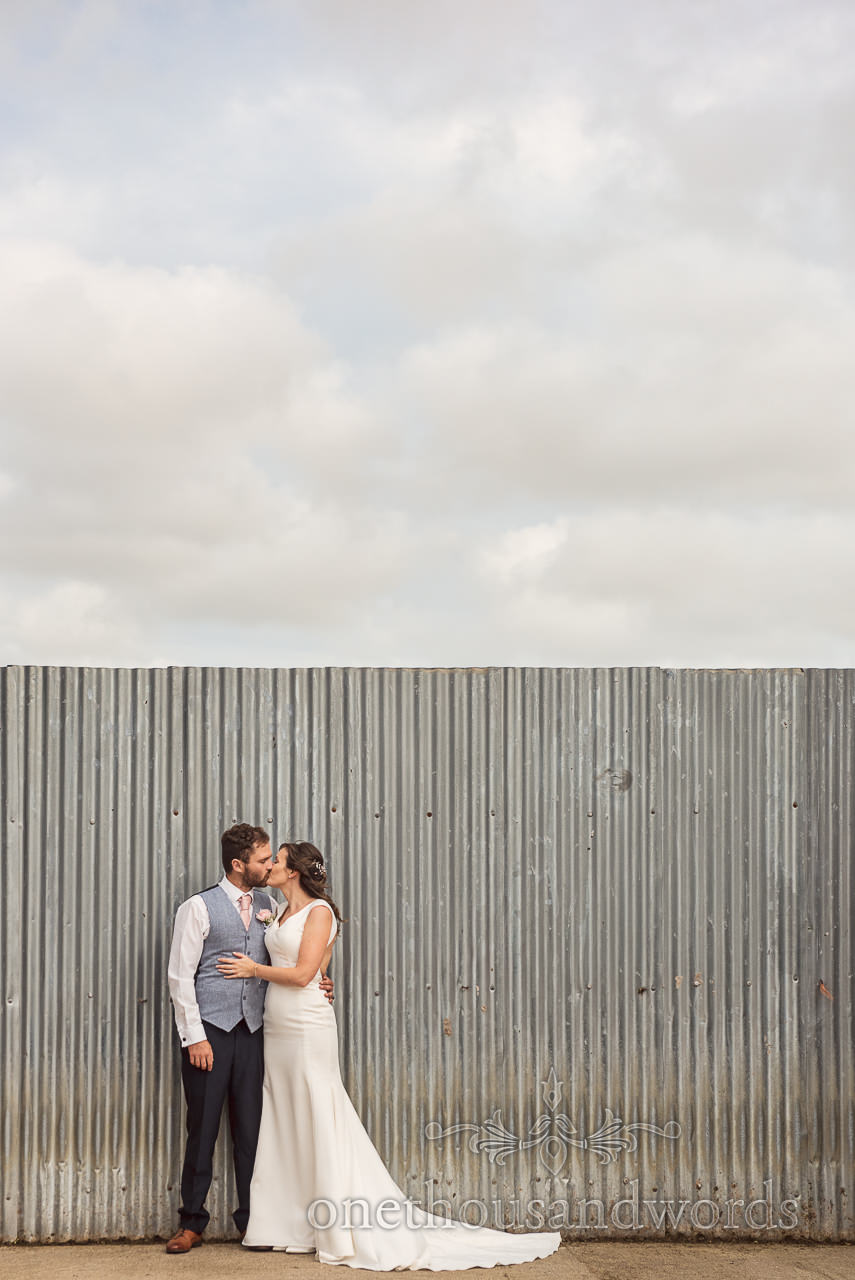 Kissing bride and groom with corrugated metal wall at Purbeck farm marquee wedding photographs by one thousand words photography
