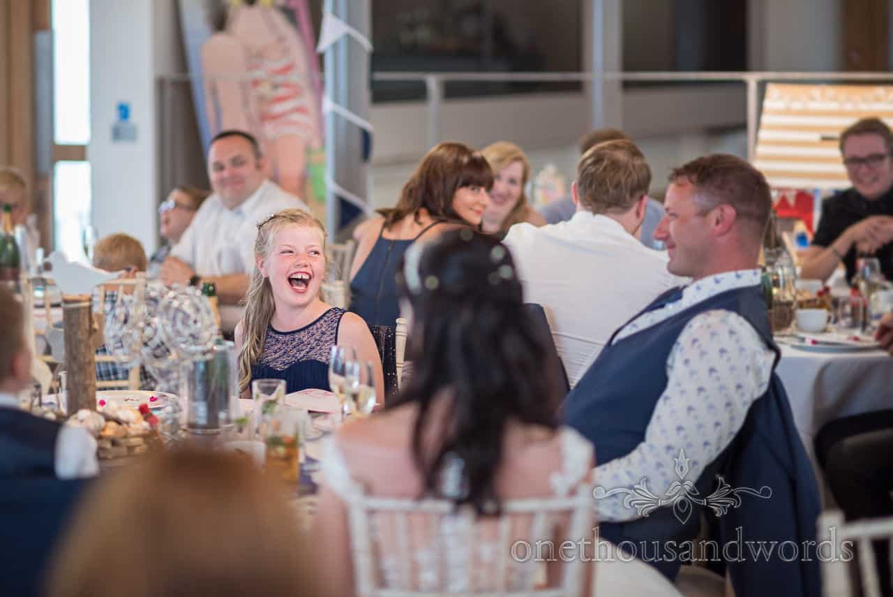 Laughing daughter sat at top table amongst wedding party bridesmaid reaction to best man's wedding speech