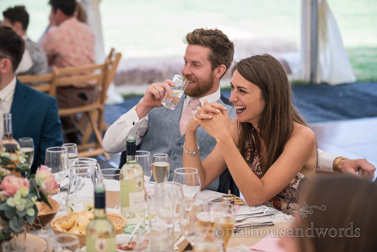 Wedding photograph of laughing guests during speeches at Purbeck farm marquee wedding photographs by one thousand words