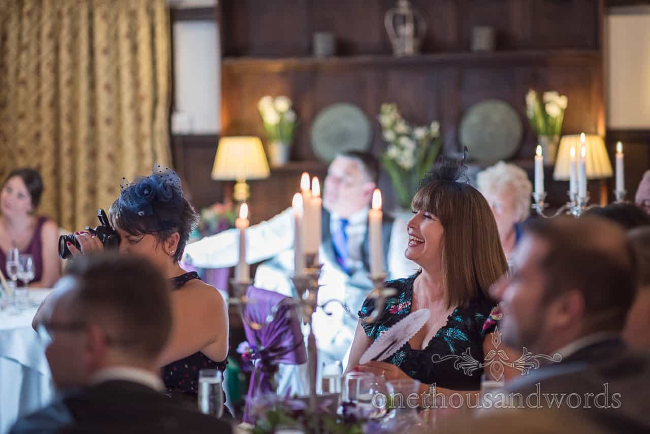Laughing wedding guests in navy blue fascinators react to candle lit wedding speeches whilst taking photographs with flash gun