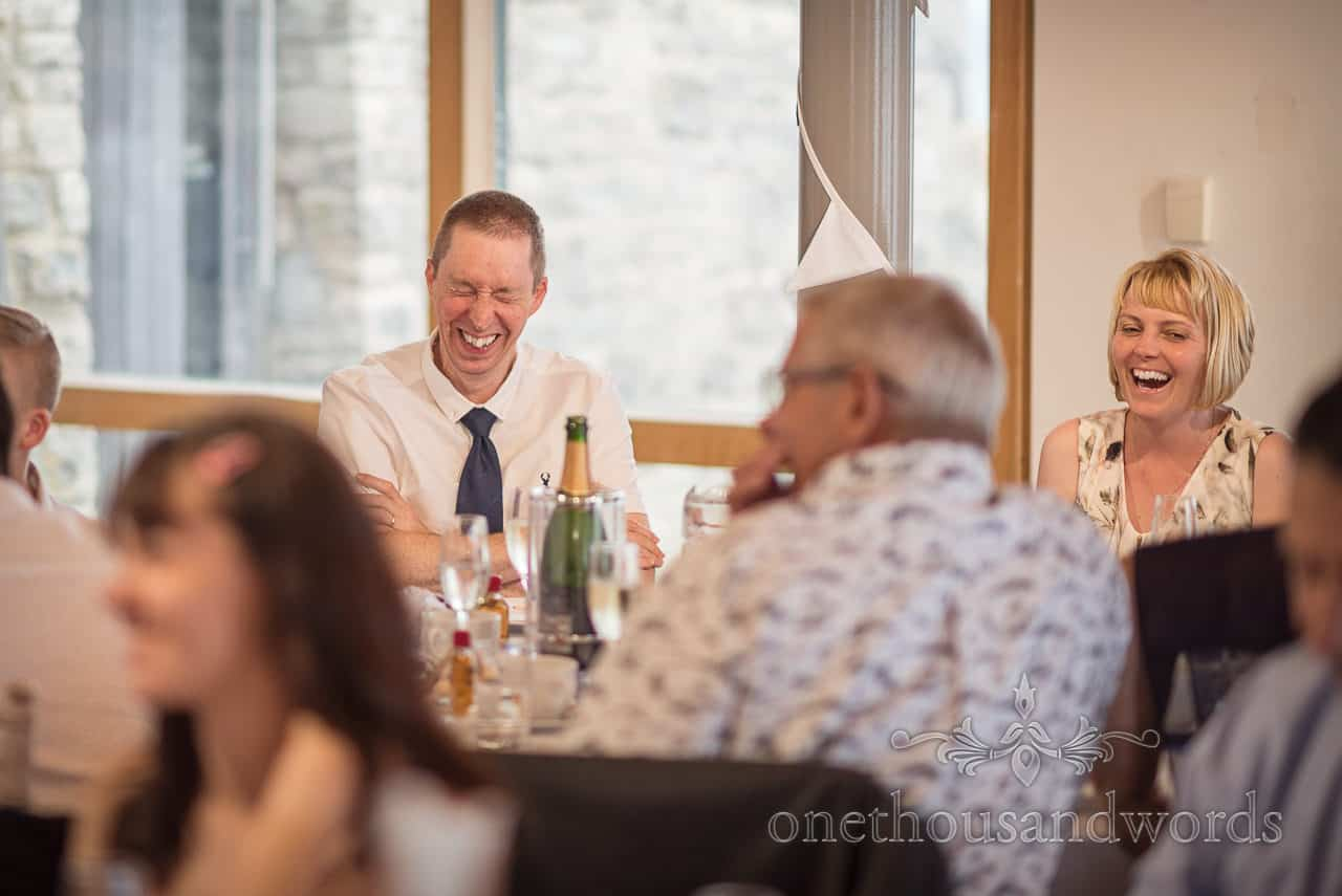 Wedding guests laughing reaction photograph to wedding breakfast speeches by one thousand words wedding photography