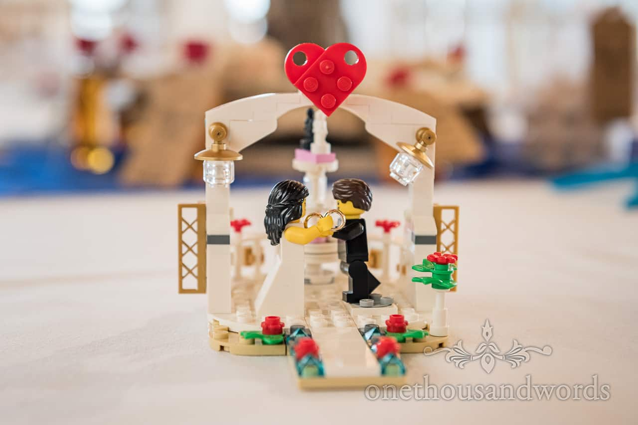 Wedding decoration detail photograph of Lego bride and groom holding gold wedding rings under love heart archway