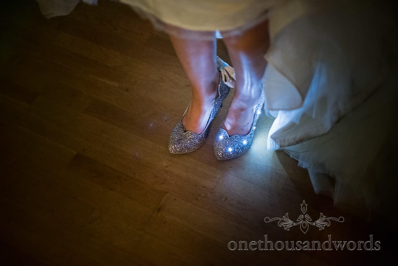 Light up Disney princess silver sparkly bridal wedding shoes under wedding dress on wooden dance floor