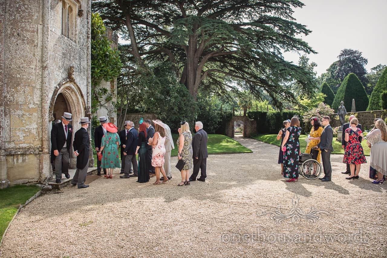Line of wedding guests arriving to be greeted by grooms men at Athelhampton House wedding venue in Dorset