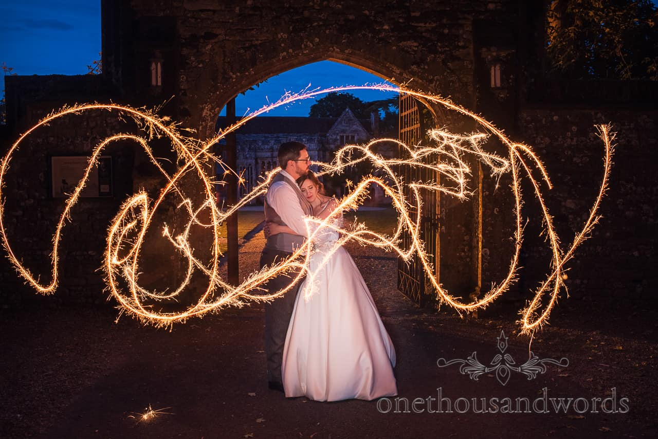 Long exposure sparklers photograph with bride and groom at Athelhampton House wedding venue at night by one thousand words