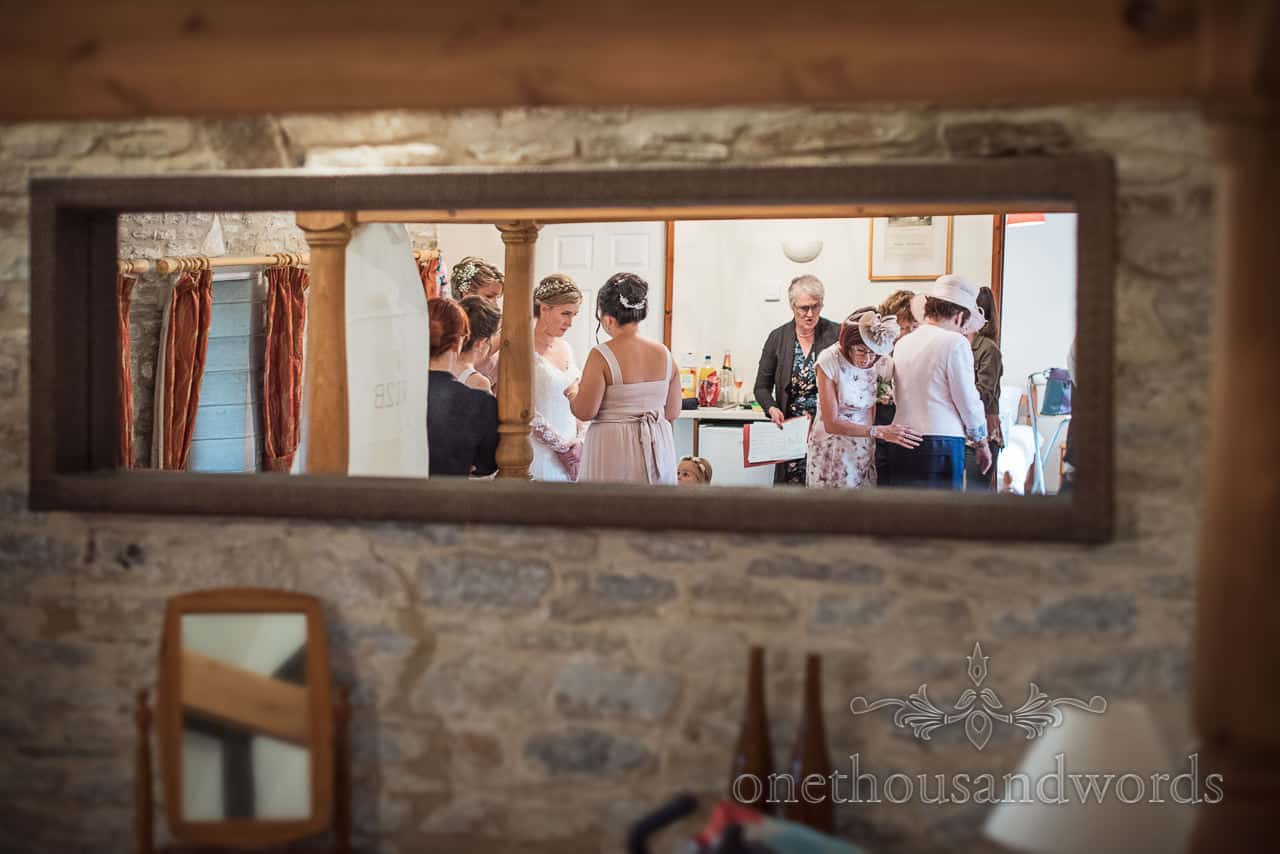 Mirror reflection of last minute preparations in bridal suite at barn wedding venue by one thousand words wedding photography