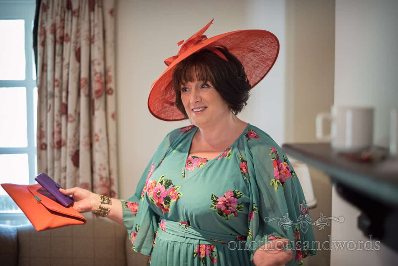 Mother of the bride in coordinated orange hat and clutch bag presents herself on wedding morning wearing green floral print dress