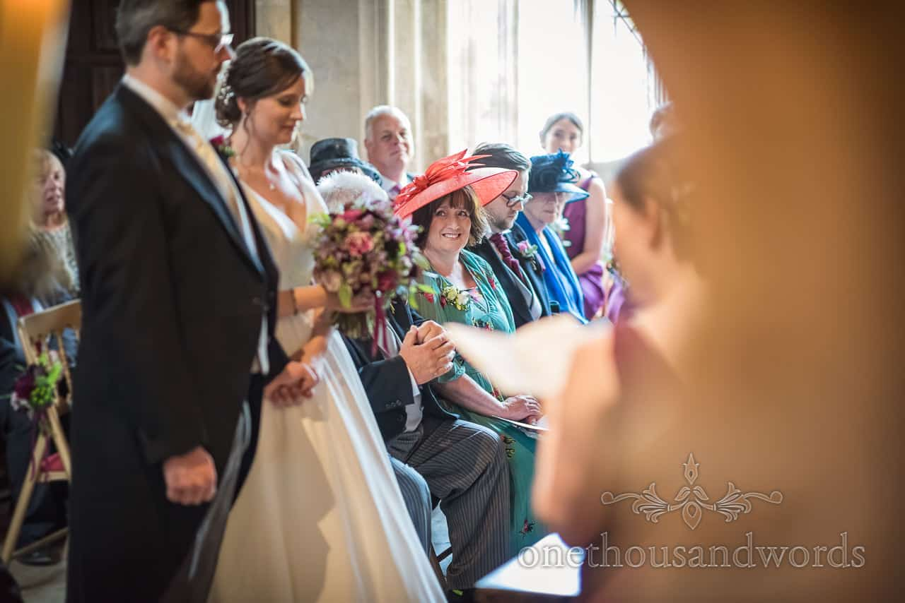Mother of the bride wearing orange hat smiling during wedding ceremony readings photograph by one thousand words photography