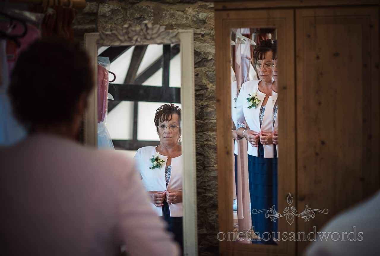 Mother checks herself in mirrors during Dorset wedding morning preparations by one thousand words wedding photography
