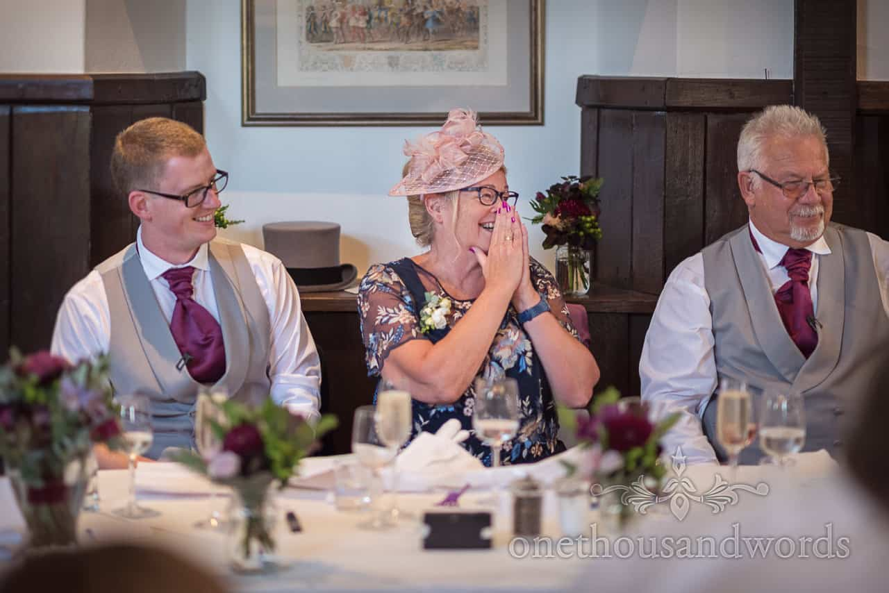 Mother of groom with groomsmen at top table wearing pink fascinator covers her mouth whilst laughing at wedding speeches