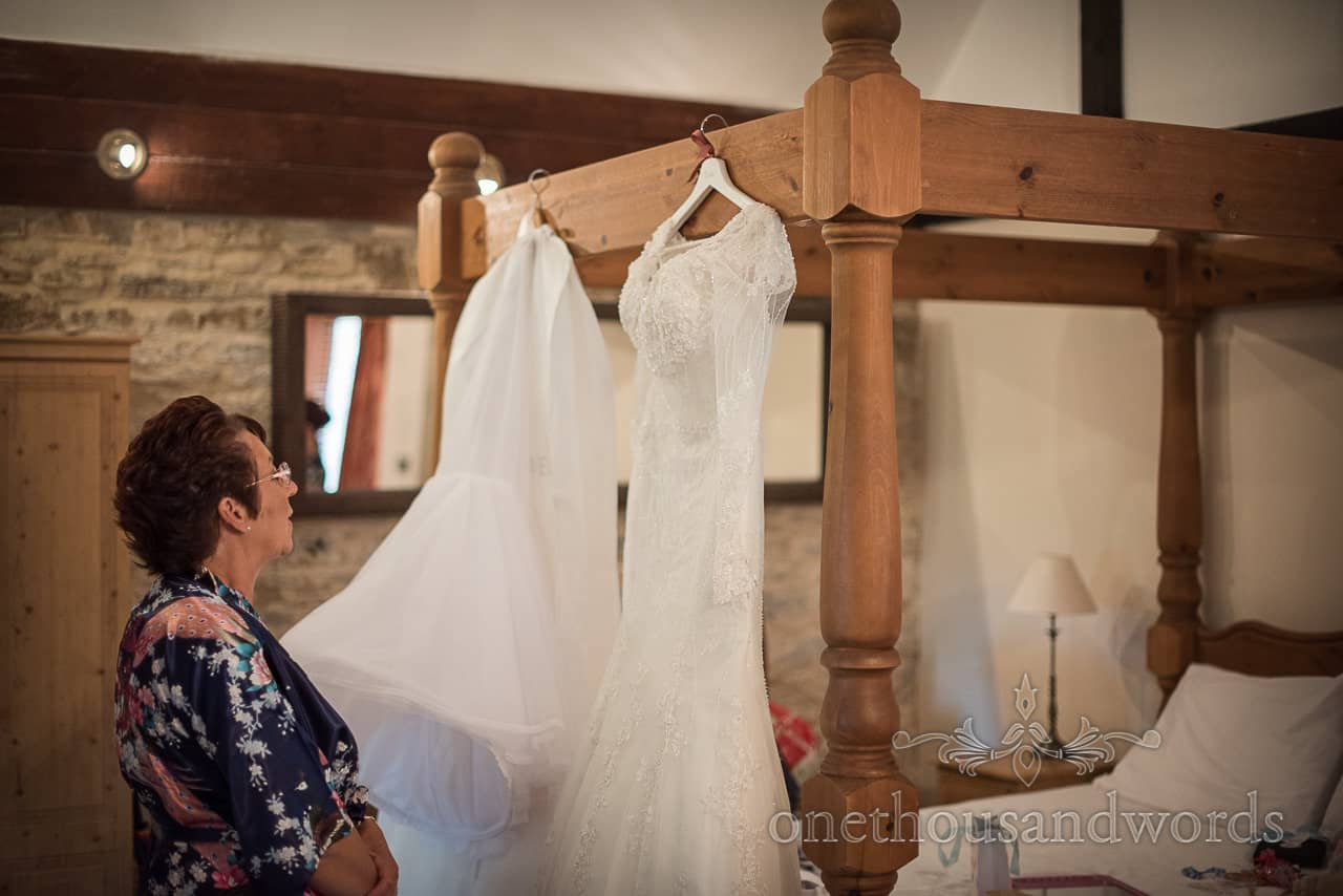 Mother of groom in dressing gown examines white wedding dress hanging on four poster bed in bridal suite on wedding morning