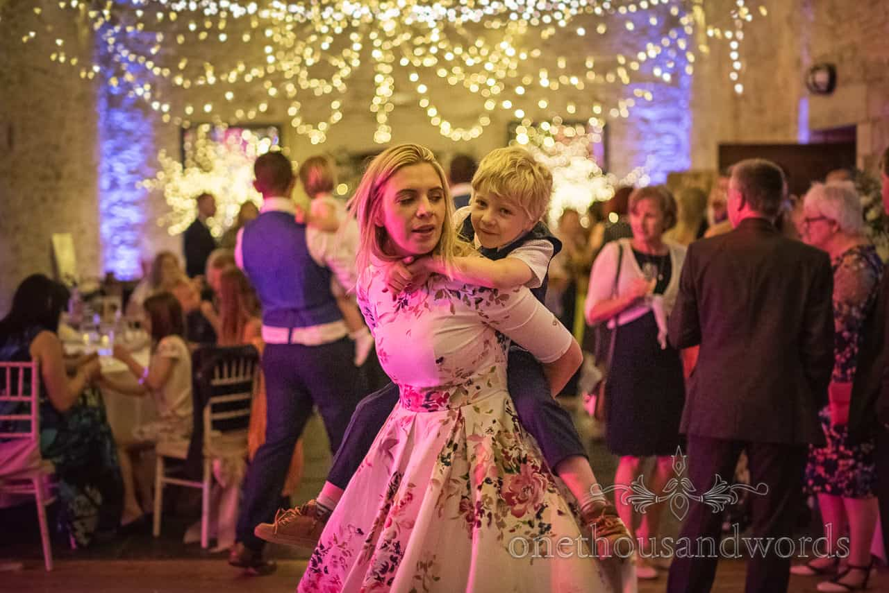 Mother and son wedding guests dance under pink disco lights during barn wedding evening reception by one thousand words