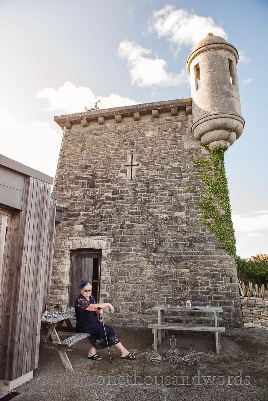 Mother of the bride with walking stick taking it easy at Purbeck Castle wedding venue by one thousand words wedding photography