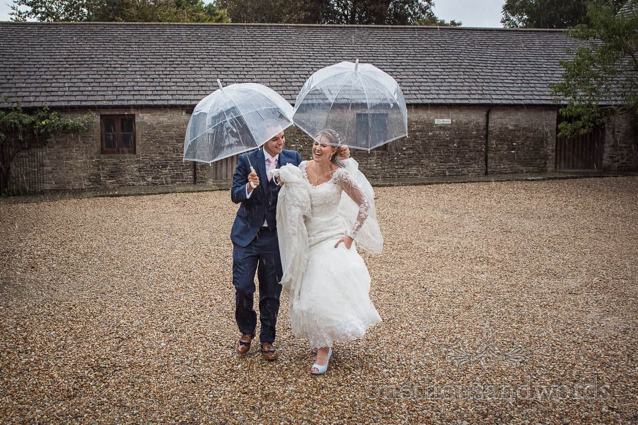 Bride and groom under clear plastic umbrellas walk across courtyard in the rain at Kingston barn wedding venue in Dorset