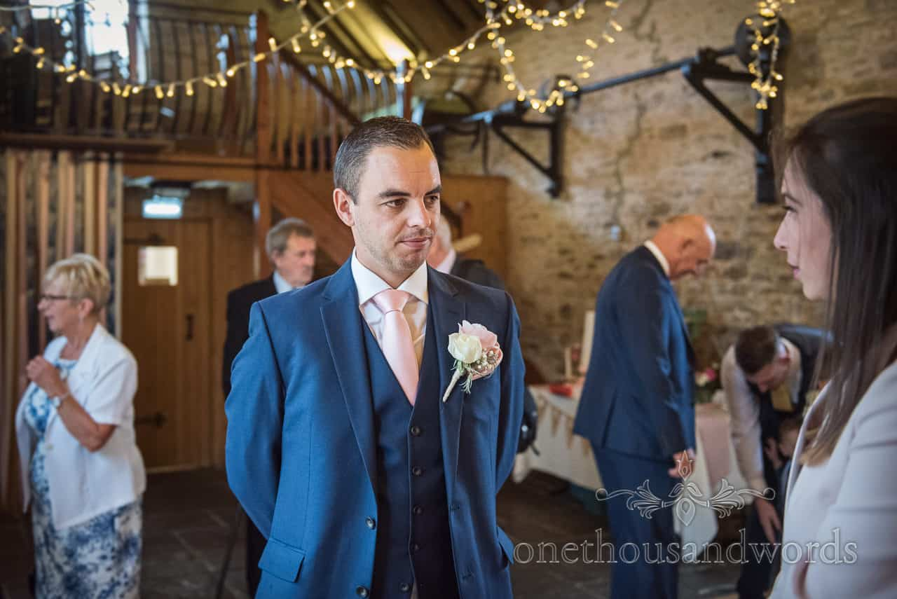 Nervous looking groom greets wedding guest just before Kingston Country Courtyard Dorset barn ceremony by one thousand words