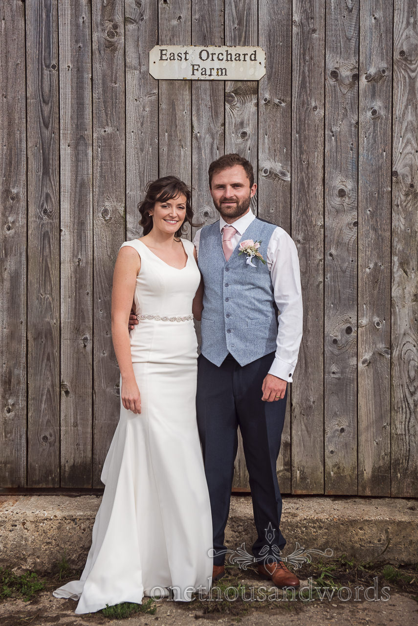 Bride and groom with East Orchard Farm wooden door and sign at Dorset farm wedding photo by one thousand words photography