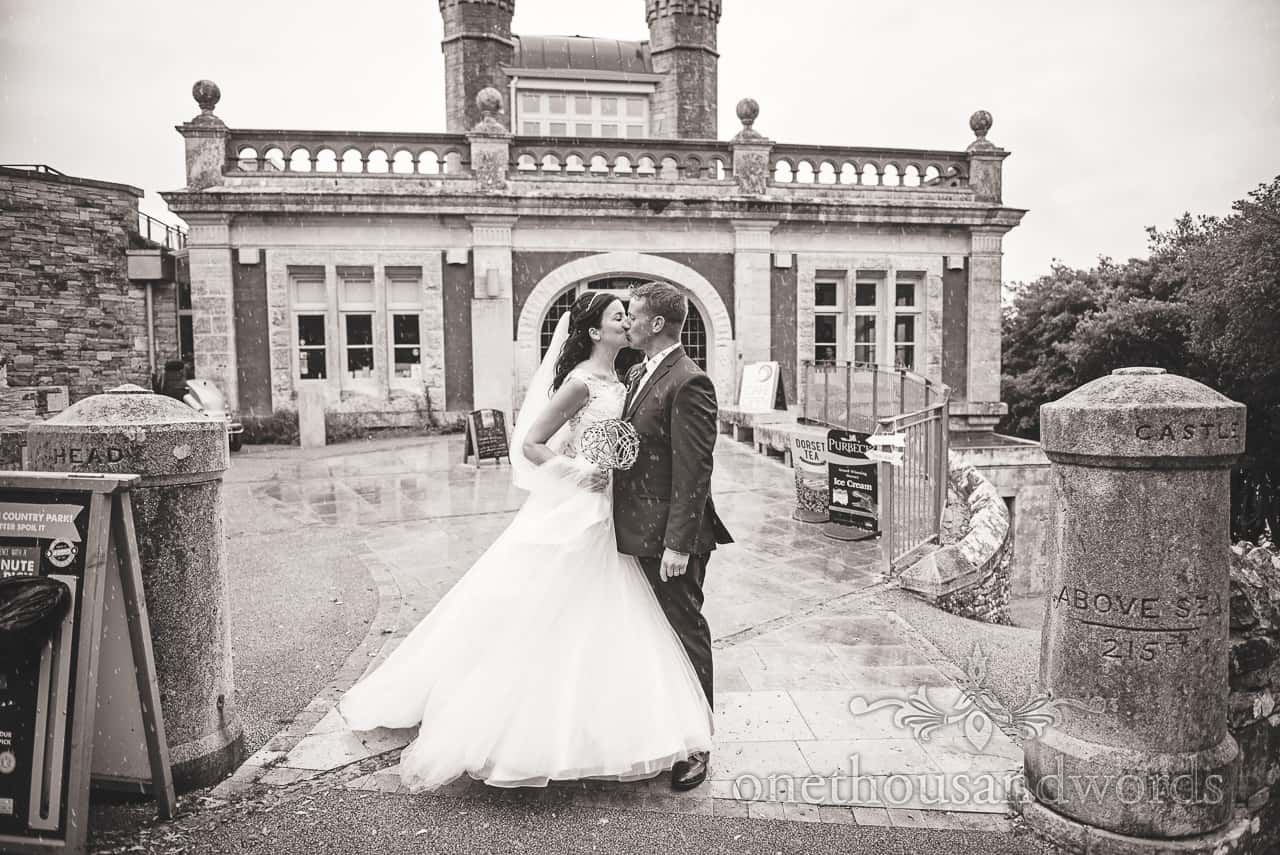 Newly weds kiss outside Durlston Castle wedding venue black and white wedding photograph by one thousand words photography