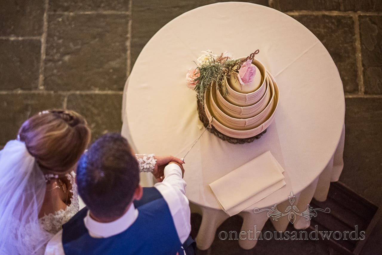 Documentary photograph taken from above of bride and groom cutting their wedding cake by one thousand words wedding photogrpahy