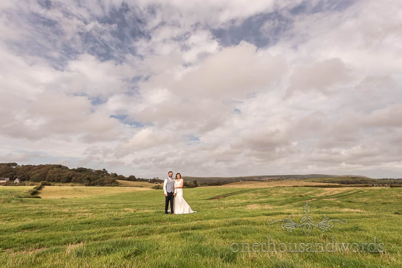 Bride and groom stand in Dorset countryside field at Purbeck farm marquee wedding photographs by one thousand words