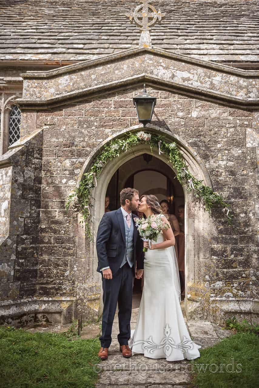 Photograph of bride and groom stopping to kiss outside Dorset stone church doorway by one thousand words wedding photography