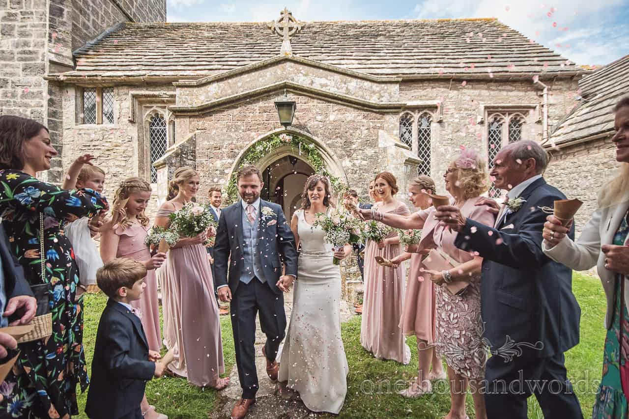 Newly weds are showered with confetti outside Purbeck, Dorset stone church wedding venue photograph by one thousand words